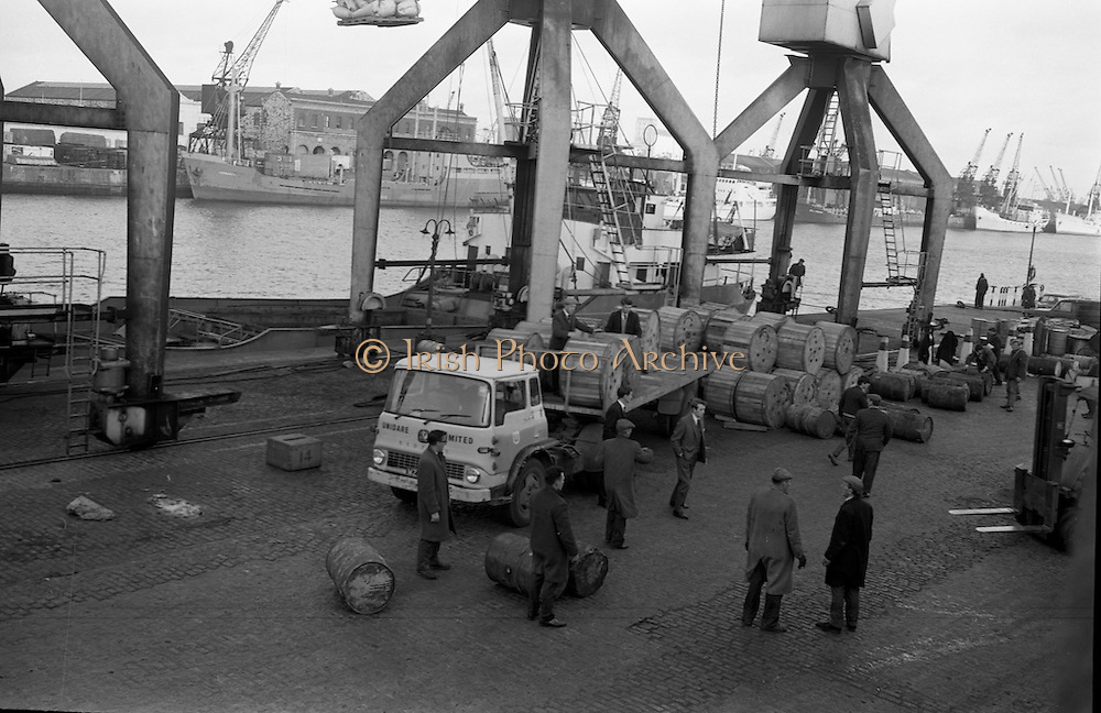 3/11/1967<br /> 11/3/1967<br /> 3 November 1967<br /> <br /> 76 Miles of Aluminium conductor cable in 42 large drums on their way to Kenya,Mozambique and Malawi from Unidare Limited of Fingals, Dublin to be used in Electricity development in these countries<br /> <br /> photo shows Mr. F.J. Shonldice Assistant to the General Sales Manager Unidore Limited and Mr. K. McCafe Export Officer watching the loading of the cable on board the S.S. Margell at the South Wall Dublin