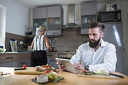Young man looking recipe on digital tablet for meal in the kitchen, Bavaria, Germany