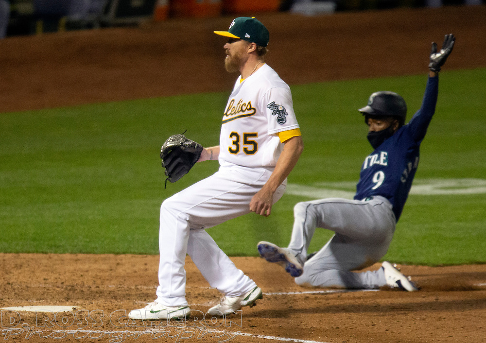 Sep 25, 2020; Oakland, California, USA; Seattle Mariners pinch runner Dee Strange-Gordon (9) slides safely home on a wild pitch by Oakland Athletics pitcher Jake Diekman (35) during the tenth inning of a Major League Baseball game at Oakland Coliseum. Mandatory Credit: D. Ross Cameron-USA TODAY Sports
