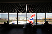 Silhouette view of passengers waiting in the terminal building for their British Airways flights from London City Airport in London, England, United Kingdom. London City Airport is an international airport located in the Royal Docks in the London Borough of Newham, east of the City of London in the Docklands area. It is an incredibly convenient airport for business travel.