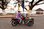An ice cream vendor rids his cart along the lake front boardwalk in Catemaco, Veracruz, Mexico. The town of 45,000 sits on the edge of the massive Lake Catemanco and is known as the city of witches and witchcraft.