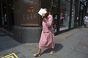 Summertime in London, England, UK. Woman shielding her face from the harsh summer sun.