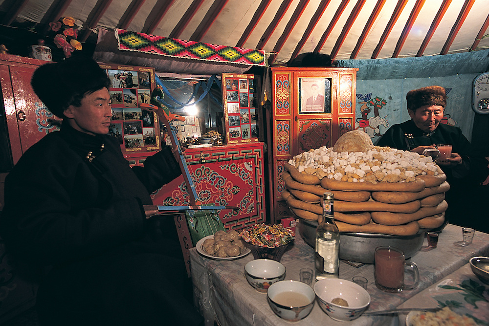Lunar New Year's table in ger<br /> Sevrei Sum, Gobi Desert<br /> Mongolia<br /> Oldest person has arms on top