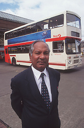 Male bus driver wearing blazer jacket and tie standing on coach station forecourt with double decker bus in background,