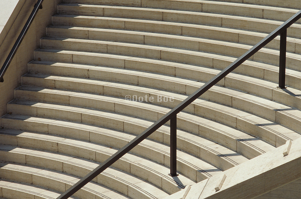 wide rounded staircase and hand rails