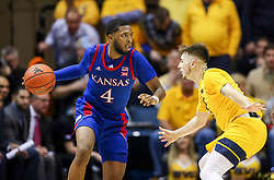 Feb 12, 2020; Morgantown, West Virginia, USA; Kansas Jayhawks guard Isaiah Moss (4) dribbles while defended by West Virginia Mountaineers guard Jordan McCabe (5) during the second half at WVU Coliseum. Mandatory Credit: Ben Queen-USA TODAY Sports