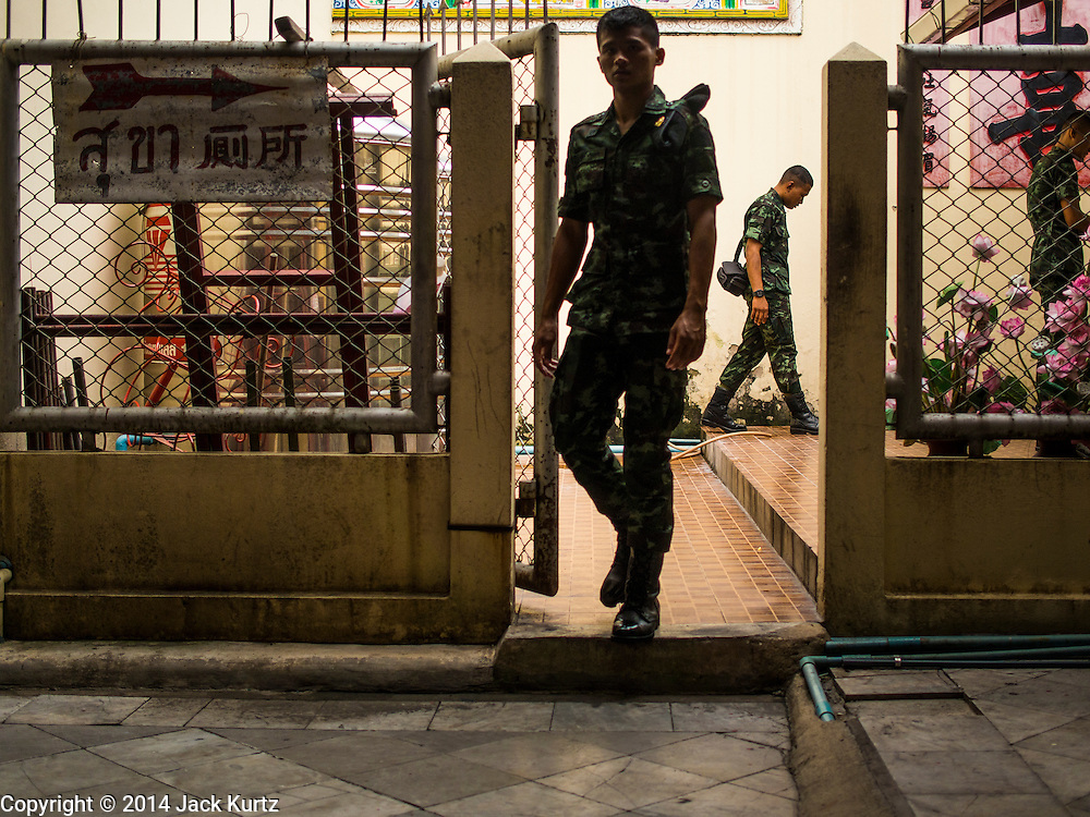 """09 AUGUST 2014 - BANGKOK, THAILAND:       Thai soldiers walk into the Ruby Goddess Shrine in the Dusit section of Bangkok. The seventh month of the Chinese Lunar calendar is called """"Ghost Month"""" during which ghosts and spirits, including those of the deceased ancestors, come out from the lower realm. It is common for Chinese people to make merit during the month by burning """"hell money"""" and presenting food to the ghosts. At Chinese temples in Thailand, it is also customary to give food to the poorer people in the community.   PHOTO BY JACK KURTZ"""