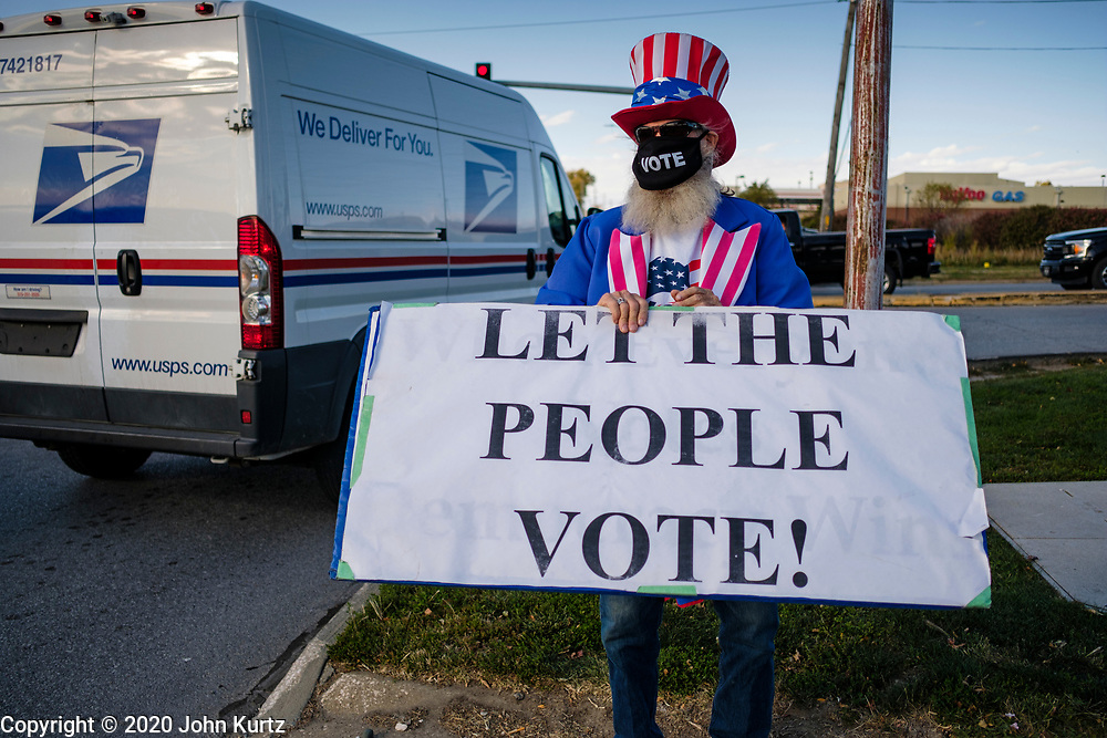 14 OCTOBER 2020 - DES MOINES, IOWA: A man urging people to vote stands in front of the entrance of the Des Moines International Airport, where President Donald Trump spoke at a campaign rally. About 10,000 people were expected to attend the rally. Trump spoke at the rally, despite testing positive for COVID-19 less than three weeks ago. The rally did not meet the CDC guidelines for a safe gathering in the time of Coronavirus.        PHOTO BY JACK KURTZ