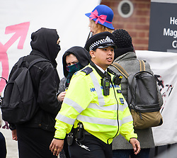 © Licensed to London News Pictures. 13/04/2018. London, UK. Police attend court to prevent a breach of the peace as Transgender activist TARA WOLF (pictured rear in blue hat) arrives at Hendon Magistrates' Court in London where she is currently on trial for assaulting radical feminist Maria Maclachlan. Tara Wolf, 26, is accused of assault by beating on Maria MacLachlan, 61, during a demonstration at Speaker's Corner, Hyde Park on September 13, last year. Photo credit: Ben Cawthra/LNP