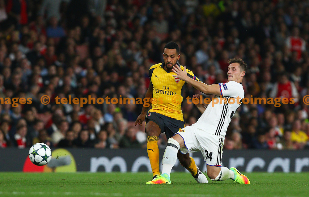 Theo Walcott of Arsenal (left) presses the defender during the UEFA Champions League Group A match between Arsenal and FC Basel at the Emirates Stadium in London. September 28, 2016.<br /> Arron Gent / Telephoto Images<br /> +44 7967 642437