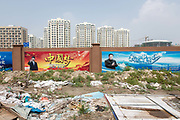 A poster featuring Xi Jinping, Chinas president, hangs on a wall as residential and commercial buildings stand in the background at the Caofeidian industrial zone near Tangshan, Hebei province, China, on Wednesday, Aug. 10, 2016. The best-performing bank in China is in a struggling city in the northeast where weeds sprout alongside the concrete skeletons of high rises in an industrial zone that mostly looks like a ghost town.