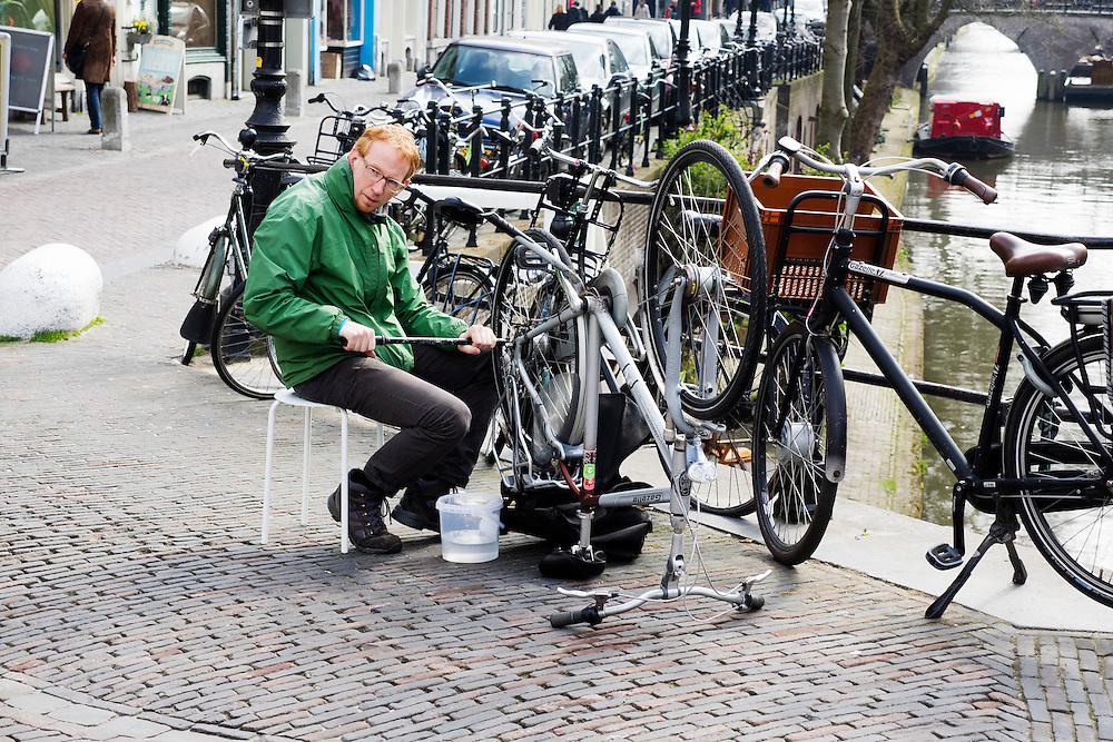 In Utrecht plakt een man de achterband van zijn fiets.<br /> <br /> In Utrecht a man is fixing the flat tire of his bicycle.