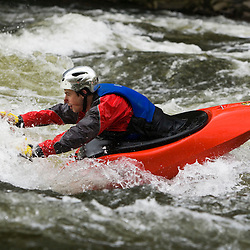 A kayaker plays in a hole in Tariffville Gorge on the Farmington River in Tariffville, Connecticut.  Class III whitewater.  Hand paddles.