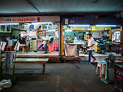 """06 FEBRUARY 2017 - BANGKOK, THAILAND: A man walks past some of the barbershops in what used to be known as Kalabok Market under the Phra Khanong Bridge in the Phra Khanong district of Bangkok. Kalabok is the Thai word for hairdresser and the market was called Kalabok because there were many barbershops and hairdressers under the bridge. In 1985, the city changed the name of the market to """"Singha Market."""" There are still about 10 small men's barbershops, most with just one barber, and four women's salons, most with one hairdresser,  under the bridge.      PHOTO BY JACK KURTZ"""