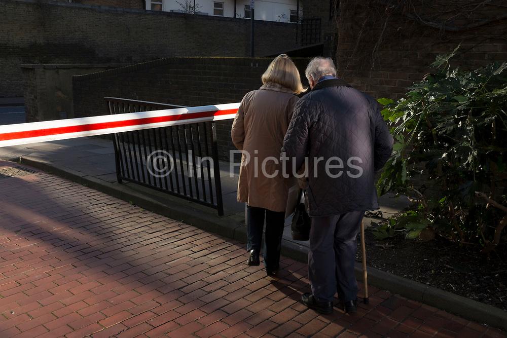 Woman helps an elderly man to walk home. London, UK.