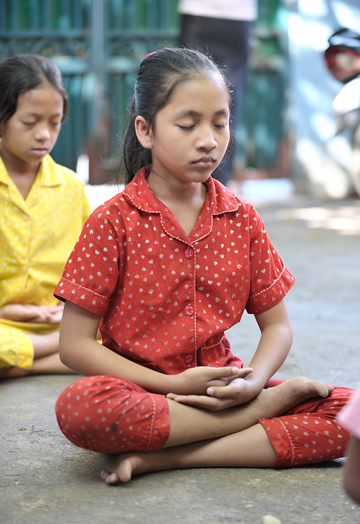 Orphans and other vulnerable children, many of them infected or affected by HIV and AIDS, engage in mediation before their morning class at a school in the Beungkak neighborhood of Phnom Penh which is run by the Salvation Centre Cambodia, an organization that works with Buddhist monks and other activists to do education and advocacy and care for people infected or affected by HIV and AIDS.