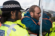 Insulate Britain spokesman Liam Norton is arrested after  a slip road from the M25 at Junction 14 close to Heathrow is blocked by Insulate Britain as part of a campaign intended to push the UK government to make significant legislative change to start lowering emissions on 27th September 2021 in Colnbrook, United Kingdom. The activists are demanding that the government immediately promises both to fully fund and ensure the insulation of all social housing in Britain by 2025 and to produce within four months a legally binding national plan to fully fund and ensure the full low-energy and low-carbon whole-house retrofit, with no externalised costs, of all homes in Britain by 2030.