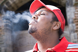 Young man standing smoking a cigarette and blowing our smoke,
