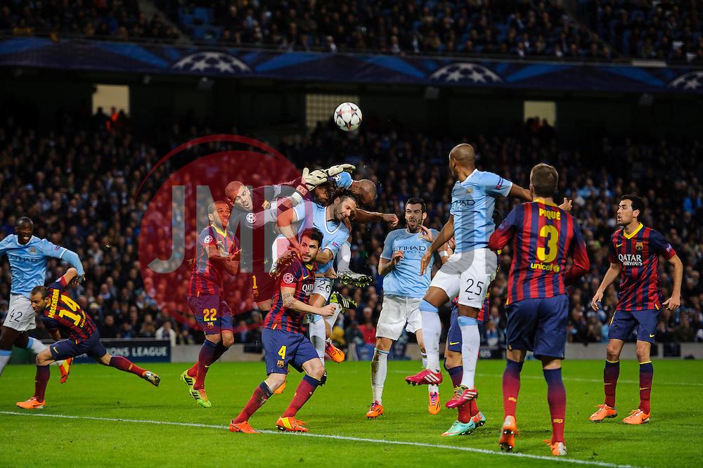 Barcelona Goalkeeper Victor Valdes (ESP) saves from Man City Defender Vincent Kompany (BEL) - Photo mandatory by-line: Rogan Thomson/JMP - Tel: 07966 386802 - 18/02/2014 - SPORT - FOOTBALL - Etihad Stadium, Manchester - Manchester City v Barcelona - UEFA Champions League, Round of 16, First leg.