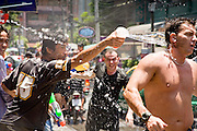 "Apr. 13, 2010 - Bangkok, Thailand: Thais throw water on a tourist Songkran festivities on a soi off of Sukhumvit Rd in Bangkok Tuesday. Songkran is the Thai New Year's holiday, celebrated from April 13 - 15. This year's official celebrations have been cancelled because of the Red Shirt protests but Thais are still marking the holiday. It's one of the most popular holidays in Thailand. Songkran originally was celebrated only in the north of Thailand, and was adapted from the Indian Holi festival. Except the Thais throw water instead of colored powder. The throwing of water originated as a way to pay respect to people, by capturing the water after it had been poured over the Buddhas for cleansing and then using this ""blessed"" water to give good fortune to elders and family by gently pouring it on the shoulder. Among young people the holiday evolved to include dousing strangers with water to relieve the heat, since April is the hottest month in Thailand (temperatures can rise to over 100°F or 40°C on some days). This has further evolved into water fights and splashing water over people riding in vehicles. The water is meant as a symbol of washing all of the bad away and is sometimes filled with fragrant herbs when celebrated in the traditional manner. Photo by Jack Kurtz"
