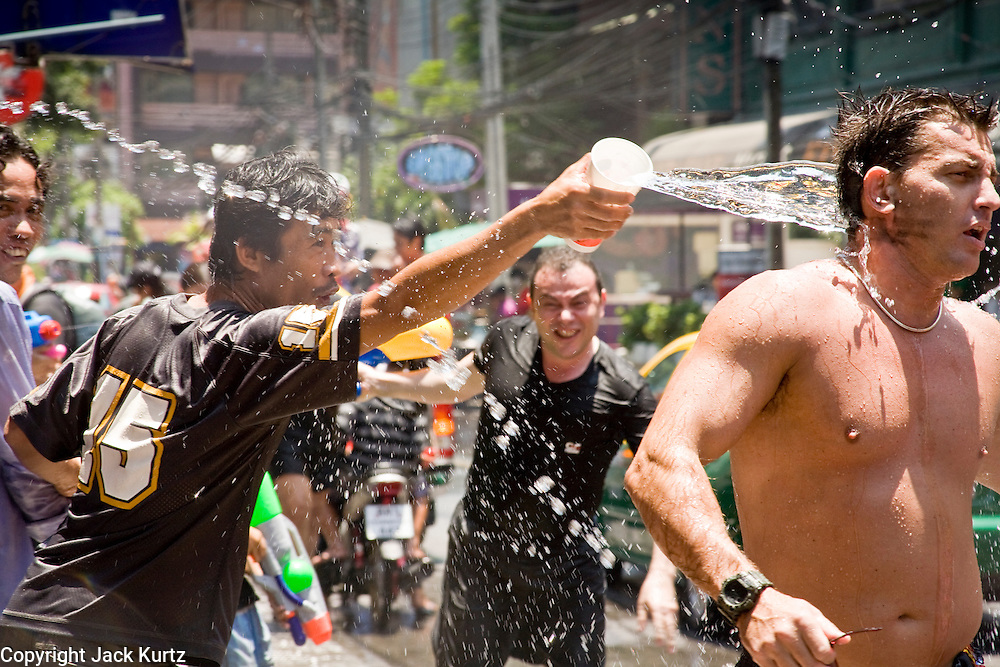 """Apr. 13, 2010 - Bangkok, Thailand: Thais throw water on a tourist Songkran festivities on a soi off of Sukhumvit Rd in Bangkok Tuesday. Songkran is the Thai New Year's holiday, celebrated from April 13 - 15. This year's official celebrations have been cancelled because of the Red Shirt protests but Thais are still marking the holiday. It's one of the most popular holidays in Thailand. Songkran originally was celebrated only in the north of Thailand, and was adapted from the Indian Holi festival. Except the Thais throw water instead of colored powder. The throwing of water originated as a way to pay respect to people, by capturing the water after it had been poured over the Buddhas for cleansing and then using this """"blessed"""" water to give good fortune to elders and family by gently pouring it on the shoulder. Among young people the holiday evolved to include dousing strangers with water to relieve the heat, since April is the hottest month in Thailand (temperatures can rise to over 100°F or 40°C on some days). This has further evolved into water fights and splashing water over people riding in vehicles. The water is meant as a symbol of washing all of the bad away and is sometimes filled with fragrant herbs when celebrated in the traditional manner. Photo by Jack Kurtz"""