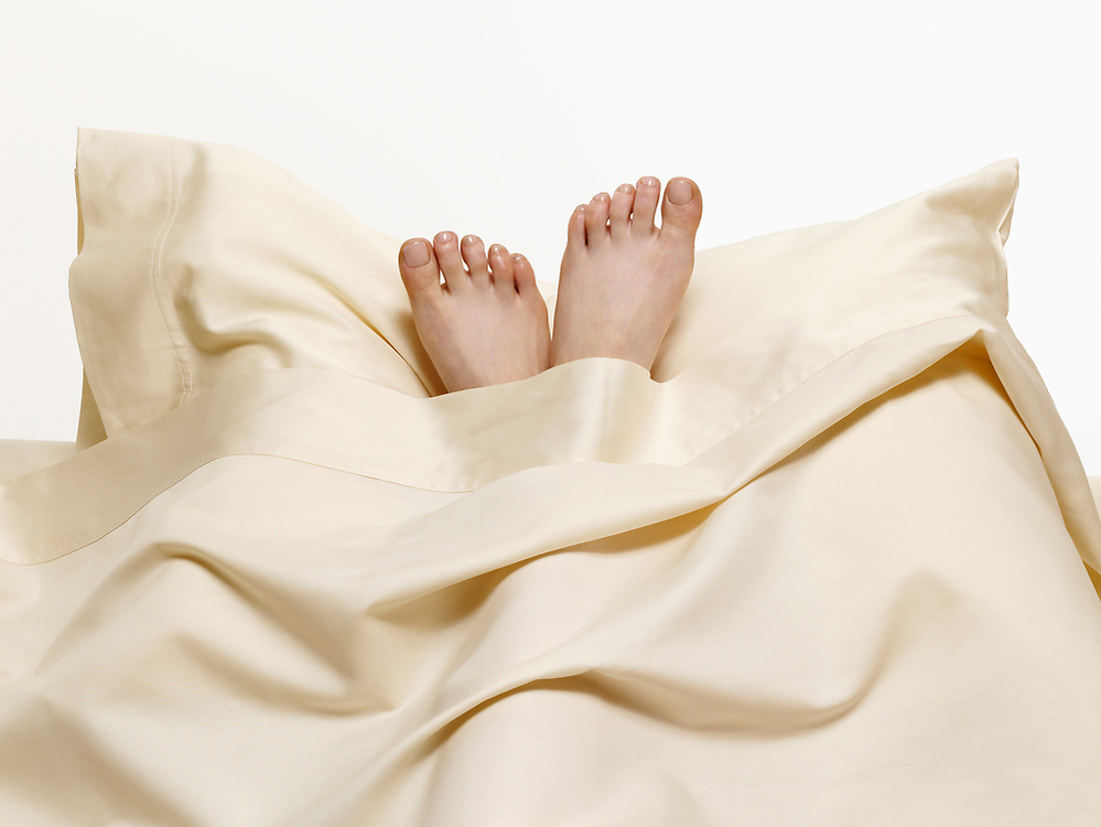 Woman's feet on pillow at head of bed
