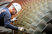 Worker inspects the blades of a gas turbine during power plant maintenance.