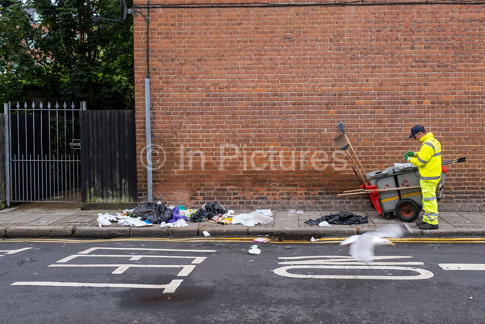A Veolia street cleaner arrives at the scene of household waste bags that have been raided by foxes and seagulls overnight on the 1st of July 2020 in Folkestone, United Kingdom.