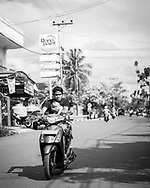 Kandangan, Indonesia - February 28, 2017: A man rides his motorbike with a napping child in his arms down a street in Kandangan, South Kalimantan.