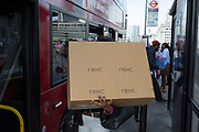 A young woman carries a large box from clothing retailer Next on to a bus heading southbound over London Bridge, on 3rd September 2018, in London England.