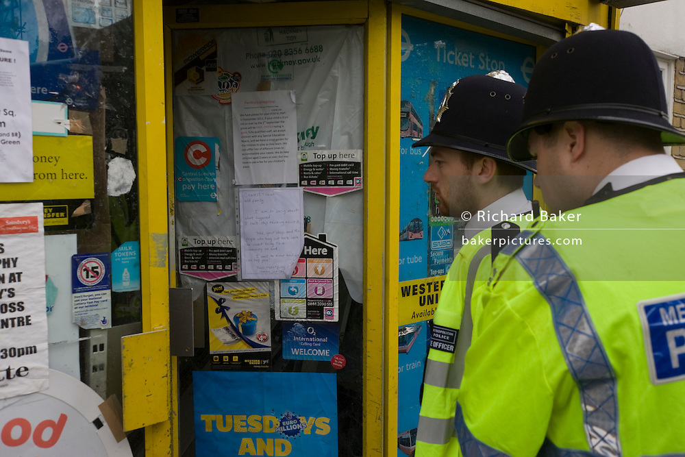 Two Metropolitian Police Officers stop to view the Clarence Road Convenience Store. After the riots of London and other UK cities, Sri Lankan-born Sivaharan (Siva) Kandiah's looted shop 'Clarence Convenience Store' in Clarence Road, Hackney.