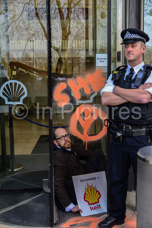 An enviroment protester super glues his hand to the front entrance of Shell oil HQ on 15th April 2019 in London, United Kingdom.  Extinction Rebellion a climate change protest group are protesting  across the centre of London and plan to block traffic for the next five days.