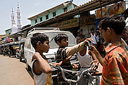 Azharuddin Ismail, 10, the child actor playing the role of 'young Salim', the brother of Jamal, protagonist of Slumdog Millionaire, the famous movie winner of 8 Oscar Academy Awards in December 2008, is taking his mobile phone back after having it shown to a 'friend' on the streets surrounding the slum where he still lives with his family next to the train station of Bandra (East), Mumbai, India. Various promises were made to lift the two young actors (Azharuddin Ismail and Rubina Ali) from poverty and slum-life but as of the end of May 2009 anything is yet to happen. Rubina's house was recently demolished with no notice as it lay on land owned by the Maharashtra train authorities and she is now permanently living with her uncle's family in a home a stone-throw away in the same slum. Azharuddin's home too was demolished in the past two weeks, as it happens every year in his case, because the concrete walls were preventing local authorities to clear a drain passing right behind it. As usual, his father is looking into restoring the walls as soon as the work on the drain has been completed.