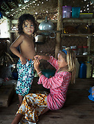 Kids helping eachother. Tobel's home, . In and around the stilt house settlement off Bodgaya island.