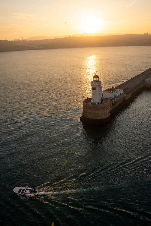A boat leaves the port in Bilbao, Spain, at sunrise, passing by fishermen at the end of the breakwater.