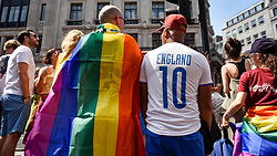 © Licensed to London News Pictures. 07/07/2018. LONDON, UK. An England fan in town to watch the England v Sweden World Cup football match views the annual Pride in London Parade, the largest celebration of the LGBT+ community in the UK.  Photo credit: Stephen Chung/LNP