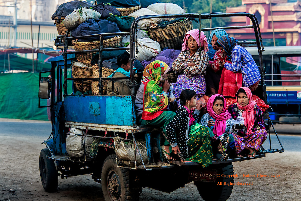 Morning Lorry Home: After the shopping at the morning market, a group of women who are dressed to stave off the morning chill, mount the back of a fully loaded lorry for the long ride home, Myinkaba Myanmar.