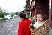 Mother with her baby in a basket on her back at Lugu Lake, Yunnan, China. Lugu Lake is located in the North West Yunnan plateau in the centre of Ninglang Yi Autonomous County in the Peoples Republic of China.