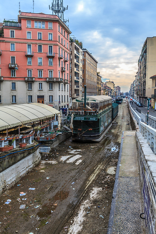 Naviglio Pavese canal in Milan, Italy. The canal system was once fundamental means of communication for the city of Milan. Canals are empty on winter time.