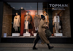 © Licensed to London News Pictures. 30/11/2020. London, UK. A woman walks past the shop front of a Topshop store on Oxford Street in London. Arcadia Group, the parent company of retail outlets Top Shop, Burton, Dorothy Perkins, Evans and Miss Selfridge, is close to going in to administration, putting putting 13,000 jobs at risk, following the economic affects of coronavirus lockdown. Photo credit: Ben Cawthra/LNP