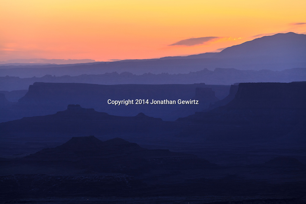 The brightening morning sky silhouettes distant ridges beyond Buck Canyon and the White Rim mesa in Canyonlands National Park, Utah.<br /> <br /> WATERMARKS WILL NOT APPEAR ON PRINTS OR LICENSED IMAGES.<br /> <br /> Licensing: https://tandemstock.com/assets/14803504