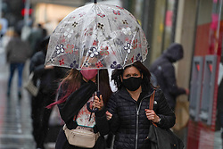 © Licensed to London News Pictures 28/10/2020. Nottingham  , UK. Shoppers wearing face masks use an umbrella to protect from the rain as they walk   in the city centre before new restrictions come into force in Nottingham. The county of Nottinghamshire will enter into Tier 3 ,from 00:01 am on Friday 30 October. Photo credit: Ioannis Alexopoulos/LNP