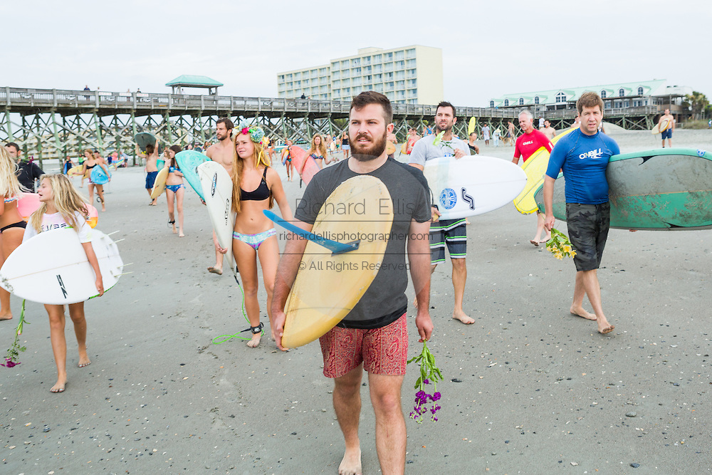 Charleston area surfers gather for a traditional memorial paddle out to honor and remember the nine people killed at the historic mother Emanuel African Methodist Episcopal Church June 27, 2015 in Folly Beach, South Carolina. Earlier in the week a white supremacist gunman killed 9 members at the historically black church.