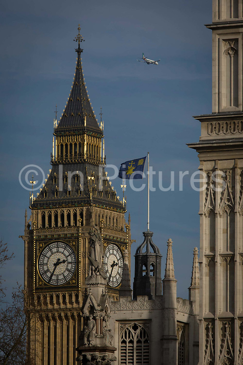 Big Ben and other Westminster architecture in central London. A jet airliner flies over the city as the sun shines on the Gothic clock tower. Westminster is a central London area within the City of Westminster lying on the River Thames' north bank. Westminster's concentration of visitor attractions and historic landmarks, one of the highest in London, includes the Palace of Westminster, Buckingham Palace, Westminster Abbey and Westminster Cathedral. The Westminster system is a democratic parliamentary system of government modelled after the politics of the United Kingdom. This term comes from the Palace of Westminster, the seat of the Parliament of the United Kingdom.e