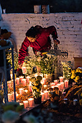 A woman lights candles on a decorated gravesite of a family member during the Day of the Dead festival October 31, 2017 in Tzintzuntzan, Michoacan, Mexico.