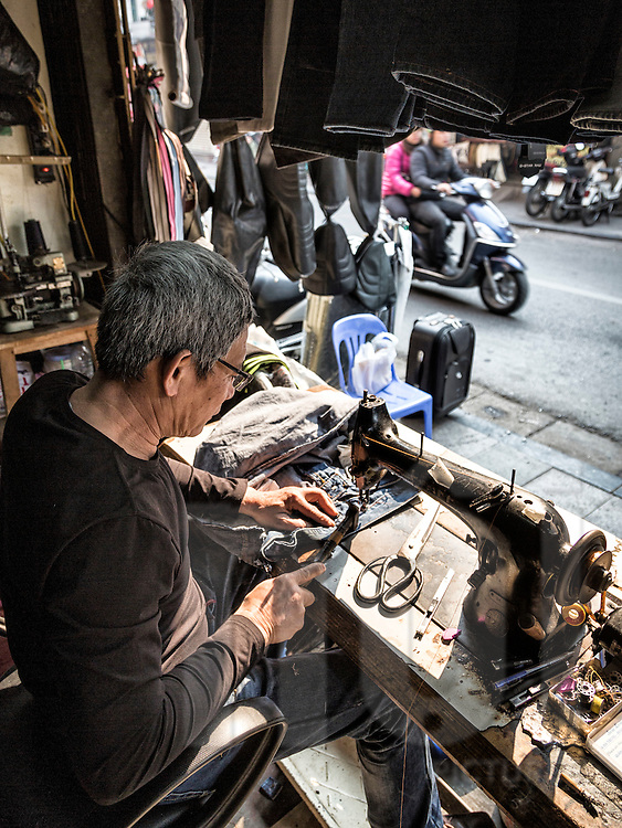 A man works on a pair of jeans in a leather shop along Hang Trung street in Hanoi's Old Quarter, Vietnam, Southeast Asia