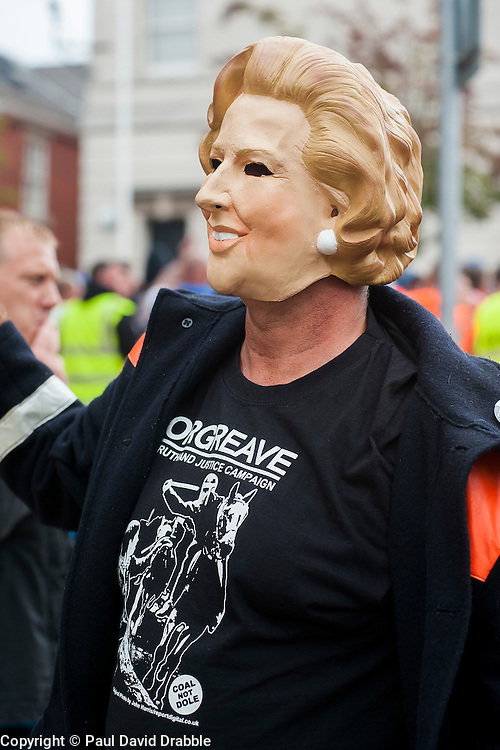 """Rotherham England<br /> 13 September 2014 <br /> A protester wearing a Margaret Thatcher Mask and ORGREAVE Truth And Justice Campaign T-Shirt Joins EDL supporters outside outside Rotherham Town Hall before the march to Rotherham Main Street Police station as part of the English Defence Leagues """"Justice for the Rotherham 1400"""" March described by an EDL Facebook Page as """"a protest against the Pakistani Muslim grooming gangs"""" on Saturday Afternoon <br /> <br /> <br /> Image © Paul David Drabble <br /> www.pauldaviddrabble.co.uk"""