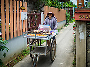 02 AUGUST 2018 - PAK KRET, NONTHABURI, THAILAND: A vender goes door to door on Ko Kret island. Ko Kret (also spelled Koh Kret) is a small island in the Chao Phraya River in Nonthaburi province north of Bangkok. It is about 2 km long and 1 km wide. It has seven main villages, the largest and most populous being Ban Mon. Ko Kret was created in 1722 when a canal was dug in the Chao Phraya River to bypass a bend. Most of the people on the island are ethnically Mon, from the hills of western Thailand and eastern Myanmar (Burma). The island is popular as a weekend daytrip from Bangkok. The island is famous for the Mon style pottery made on the island.      PHOTO BY JACK KURTZ