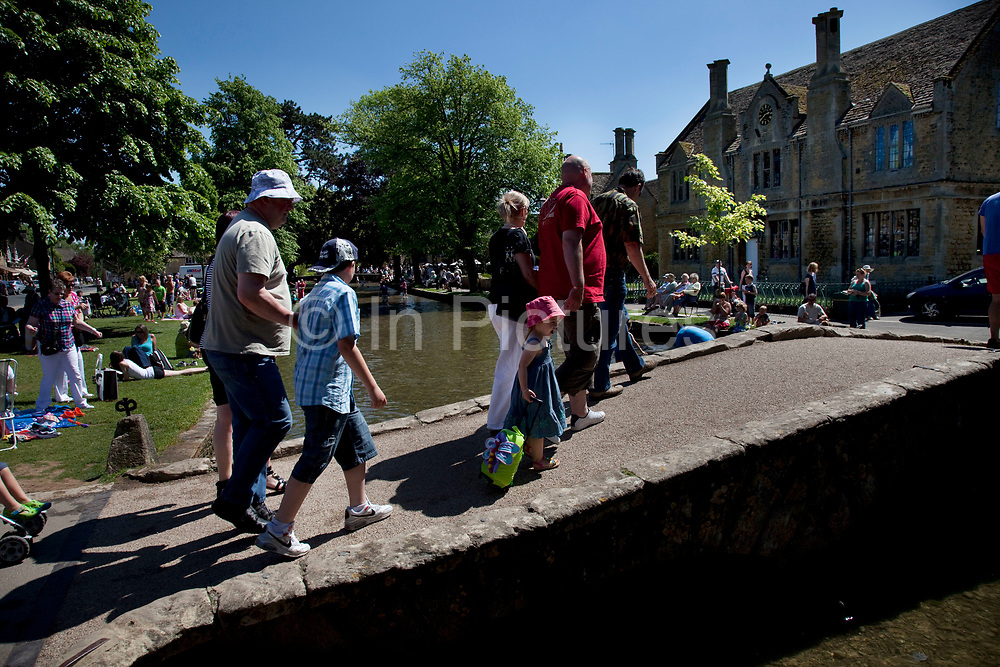 Crowds of visitors at Bourton-on-the-Water in The Cotswolds, Gloucestershire, UK.  It is known as the 'Venice of the Cotswolds' because of the bridge-spanned stream that runs through the village, this is one of the most popular places to visit in the area. Popular with both the English themselves and international visitors from all over the world, the area is well known for gentle hillsides 'wolds', outstanding countryside, sleepy ancient limestone villages, historic market towns and for being so 'typically English' where time has stood still for over 300 years. Throughout the Cotswolds stone features in buildings and stone walls act as a common thread in seamlessly blending the historic towns & villages with their surrounding landscape. One of the most 'quintessentially English' and unspoiled regions of England.