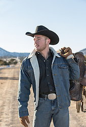 cowboy on a dirt road holding a saddle over his shoulder